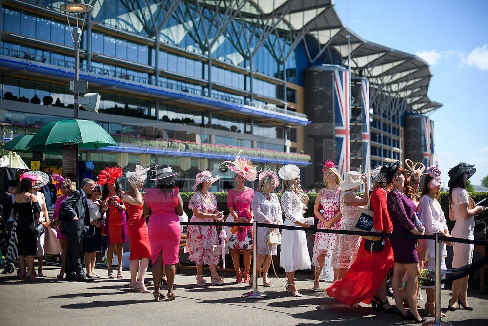 © Licensed to London News Pictures. 21/06/2018. London, UK. Racegoers wait to have their photograph taken at Ladies Day at Royal Ascot at Ascot racecourse in Berkshire, on June 21, 2018. The 5 day showcase event, which is one of the highlights of the racing calendar, has been held at the famous Berkshire course since 1711 and tradition is a hallmark of the meeting. Top hats and tails remain compulsory in parts of the course. Photo credit: Ben Cawthra/LNP