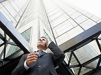 Businessman using mobile phone outside office (low angle view)