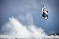 Professional rider David Tyburski skies over reef with wave crashing in background