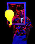 Young man with glowing shirt, glasses, frame and large lightbulb.Black light
