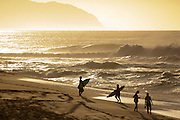 Surfers on the beach on Oahu's North Shore, Hawaii