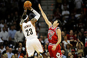 Apr 19, 2010; Cleveland, OH, USA; Cleveland Cavaliers forward LeBron James (23) shoots over Chicago Bulls guard Kirk Hinrich (12) during the fourth period in game two in the first round of the 2010 NBA playoffs at Quicken Loans Arena. The Cavaliers beat the Bulls 112-102. Mandatory Credit: Jason Miller-US PRESSWIRE