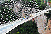 ZHANGJIAJIE, CHINA - JUNE 25:<br /> <br /> Visitors view the glass-bottomed bridge receiving a safety test at Zhangjiajie Grand Canyon on June 25, 2016 in Zhangjiajie, Hunan Province of China. World\'s tallest and longest glass-bottomed bridge has been completed and took a global broadcast through television and internet medias to show its safety. More than thirty citizens and visitors thumped the bridge with hammer in the test event. <br /> ©Exclusivepix Media