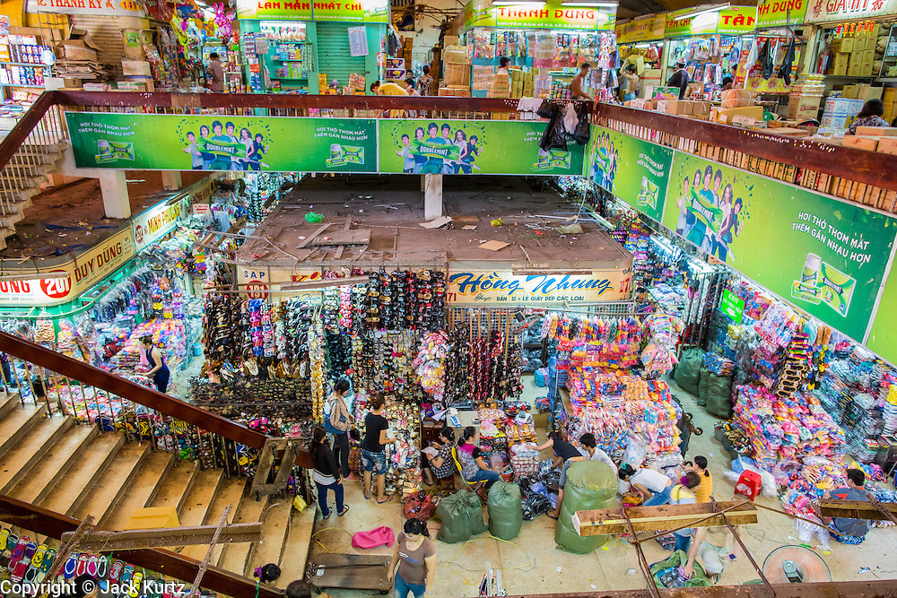 "12 APRIL 2012 - HO CHI MINH CITY, VIETNAM: Overview of an interior aisle in Binh Tay Market. The market is warren of narrow halls and alleys and steep staircases and still relies on manual labor to move goods. Binh Tay market is the largest market in Ho Chi Minh City and is the central market of Cholon. Cholon is the Chinese-influenced section of Ho Chi Minh City (former Saigon). It is the largest ""Chinatown"" in Vietnam. Cholon consists of the western half of District 5 as well as several adjoining neighborhoods in District 6. The Vietnamese name Cholon literally means ""big"" (lon) ""market"" (cho). Incorporated in 1879 as a city 11 km from central Saigon. By the 1930s, it had expanded to the city limit of Saigon. On April 27, 1931, French colonial authorities merged the two cities to form Saigon-Cholon. In 1956, ""Cholon"" was dropped from the name and the city became known as Saigon. During the Vietnam War (called the American War by the Vietnamese), soldiers and deserters from the United States Army maintained a thriving black market in Cholon, trading in various American and especially U.S Army-issue items.     PHOTO BY JACK KURTZ"