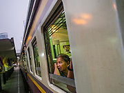 20 MARCH 2015 - BANGKOK, THAILAND: A passenger on a 3rd class train going from Bangkok to Kabin Buri looks out the window as the train leaves Bangkok. The State Railways of Thailand (SRT), established in 1890, operates 4,043 kilometers of meter gauge track that reaches most parts of Thailand. Much of the track and many of the trains are poorly maintained and trains frequently run late. Accidents and mishaps are also commonplace. Successive governments, including the current military government, have promised to upgrade rail services. The military government has signed contracts with China to upgrade rail lines and bring high speed rail to Thailand. Japan has also expressed an interest in working on the Thai train system. Third class train travel is very inexpensive. Many lines are free for Thai citizens and even lines that aren't free are only a few Baht. Many third class tickets are under the equivalent of a dollar. Third class cars are not air-conditioned.   PHOTO BY JACK KURTZ