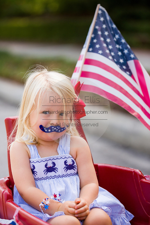 A young girl wearing patriotic costume rides in a decorated wagon during the I'On neighborhood Independence Day parade July 4, 2015 in Mt Pleasant, South Carolina.