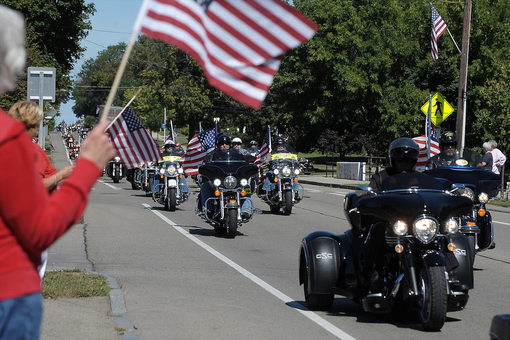 Mount Morris resident Betty Barnhardt (left) holds a flag as Patriot Guard riders make their way past the Mount Morris Veterans Memorial Park on Route 36 as the Patriot Guard escorts veterans remains to the Bath National Cemetery on September 6, 2013.