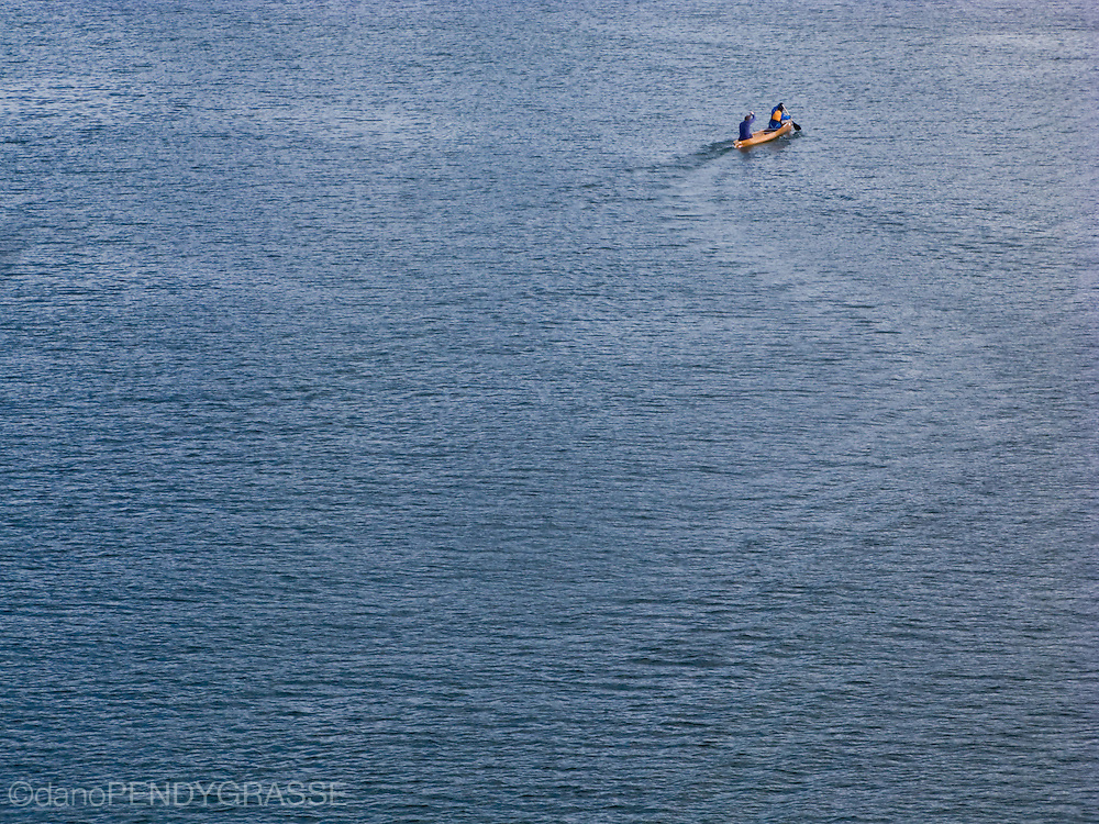 """a canoe cuts an """"s"""" into the surface of False Creek. Vancouver, British Columbia, Canada."""