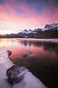 The sun rises over the 3 Sisters on the Bow River in the Canadian Rockies in Canmore.