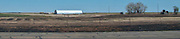 a lone farmhouse in flat rural west Texas along interstate 20  with burned grass surrounding the farm buildings panorama