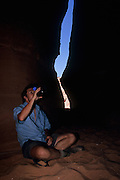 Hiker resting in a slot canyon, Coyote Gulch, Grand Staircase-Escalante National Monument, Utah