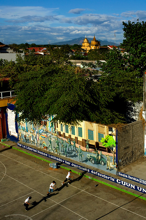 Boys playing soccer in a park in front of a revolutionary war mural in Leon, Nicaragua. The Iglesia de la Recoleccion can be seen in the background.