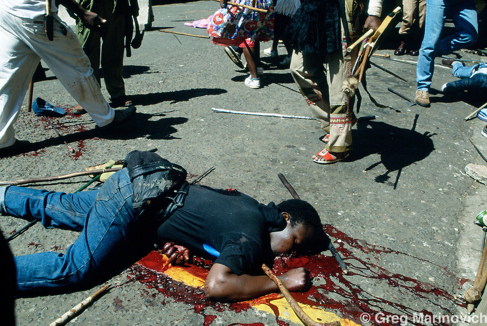Johannesburg, South Africa, 1994. A dead man lies in the street after African National Congress guards opened fire on Inkatha Freedom Party marchers when they approached the ANC headquarters of Shellhouse, Johannesburg 1994. Many IFP supporters killed and wounded. Others were shot from the rooftops by persons unknown at the nearby Library Gardens. Johannesburg, South Africa