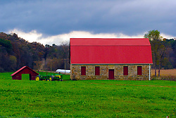 October 2009:  As storm clouds move in, the bright red roof of a stone barn and green John Deere tractors shine amid the deep lush green grass of a pasture north east of Galena. Sights to see in and around Galena Illinois.