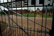 Nederland, Vught , 20030125. AMA Campus in Den Bosch. Het hek op de campus met opschrift: &quot;Isabella&quot;, gebouwen op de achtergrond.<br /> Het asielzoekerscentrum in de voormalige Isabella-kazerne in Vught is in september 2002 omgebouwd tot de eerste Nederlandse campus voor alleenstaande minderjarige asielzoekers (ama's). In het centrum moeten jongeren tussen 15 en 17 jaar worden voorbereid op een terugkeer naar hun moederland. <br /> Het is een  experiment, dat een jaar gaat duren. De ama-campus is het gevolg van het strengere beleid dat de vorige staatssecretaris van Justitie, Kalsbeek, voor de ama's in gang heeft gezet. Het Centraal Orgaan opvang Asielzoekers (COA) schotelt hen een strak dagprogramma voor, waarin onderwijs en recreatie de voornaamste elementen zijn. Het is de bedoeling dat zij het terrein niet verlaten, maar het is juridisch onmogelijk om de ama's dat te verbieden.