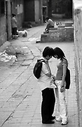 A young couple share a romantic moment in a Beijing hutong, or alley way.