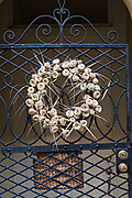 A wrought iron gate with a palmetto rose Christmas wreath at a historic home on Tradd Street in Charleston, SC.