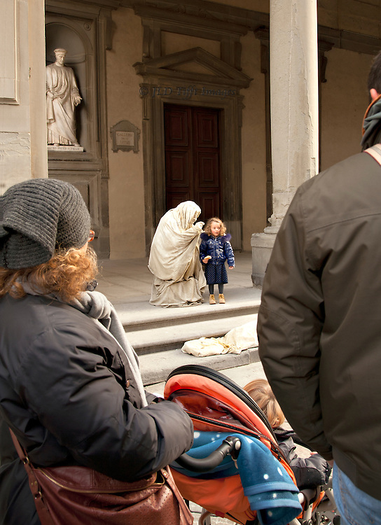 """Parents with a stroller, seen from behind, watch a """"living statue"""" hunker down to speak with a little girl.  Onlookers in the foreground, viewpoint over their shoulders"""