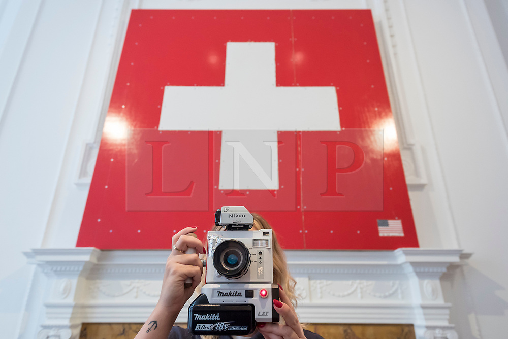 """© Licensed to London News Pictures. 05/10/2018. LONDON, UK. One of the artist's assistant takes a photograph next to the Swiss flag. Preview of """"Swiss Passport Office"""" by American artist Tom Sachs at Galerie Thaddaeus Ropac in Mayfair.  To coincide with Frieze Week, the gallery will remain open for 24 hours from 6pm 5 October to 6pm 7 October for the issuing of serial-numbered Tom Sachs Swiss passports for visitors.  The installation reflects the concerns relating to Brexit, Syria and Donald Trump's immigration policies and challenges the notion of global citizenship.  Photo credit: Stephen Chung/LNP"""