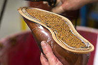 Cork is filled into the bedding for one of the hand made shoes at Allen Edmunds shoe Company sit on a shelf at the companies headquarters in Port Washington, Wisconsin April 12, 2011.  Darren Hauck