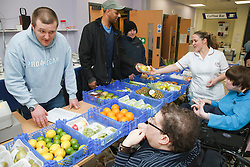 Clients buying fresh vegetables form a stall run by people with learning disabilities at a resource for people with physical and sensory impairment.