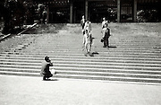 person taking picture of men walking down stairs at a temple Japan 1960s