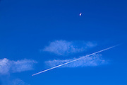 airplane and vapour trail In a blue sky with a halve moon