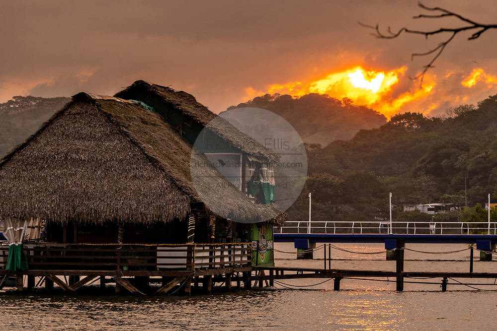 Sunset over a thatched roof restaurant along the shore of Lake Catemaco at sunset in Catemaco, Veracruz, Mexico. The tropical freshwater lake at the center of the Sierra de Los Tuxtlas, is a popular tourist destination and known for free ranging monkeys, the rainforest backdrop and Mexican witches known as Brujos.