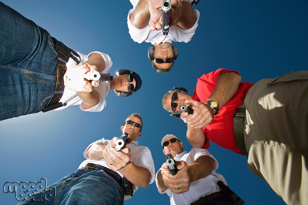 Group of people aiming guns in circle, low angle view