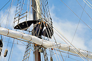 Sailing ship mast detail showing sail furled on yardarm, mast top, shrouds, lines, rigging and halyards