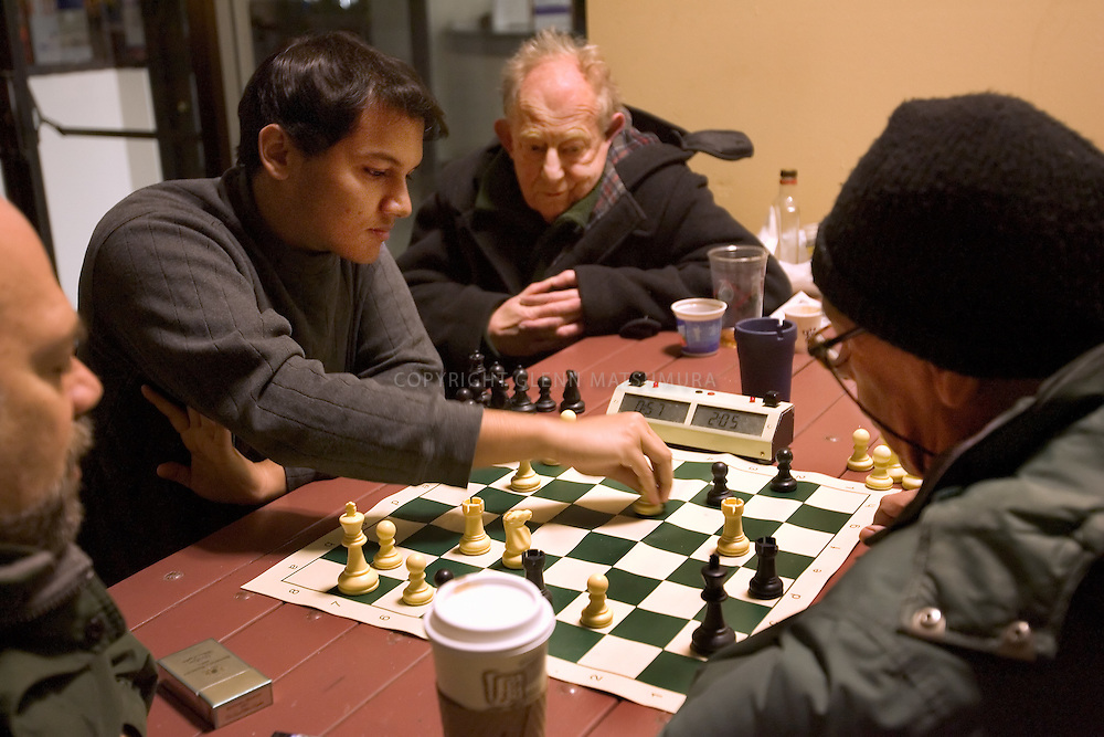Stanford after dark. Sujey Subramanian playing chess outside Tressider.