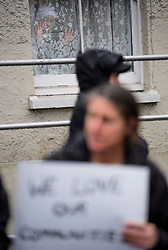 © Licensed to London News Pictures. 07/01/2017. London, UK. A young muslim girl looks out of a window as members of Kent Anti-Racism Network demonstrate outside Mote Road Islamic centre mosque in Maidstone, Kent as far-right group The South East Alliance protest against expansion of the mosque. Plans to redevelop Maidstone Mosque into a purpose-built centre with three shops have been approved by  Maidstone Borough Council. A counter demonstration is Organised by The Kent Anti-Racism Network. . Photo credit: Ben Cawthra/LNP