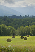 Farm field with hay bales and mountains in the background.