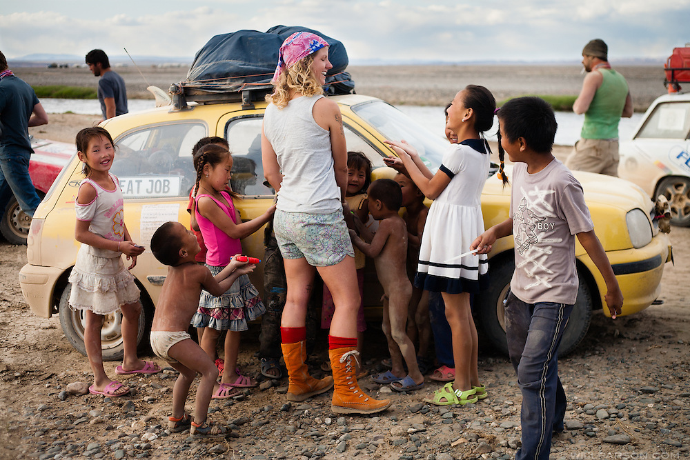 Local children ask Bones Latham of Team Great Job! for candy while her team and several others wait to ford a small river west of Bayan-Khongor, Mongolia