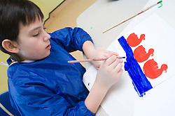 Young boy taking part in a craft activity at his local leisure centre,