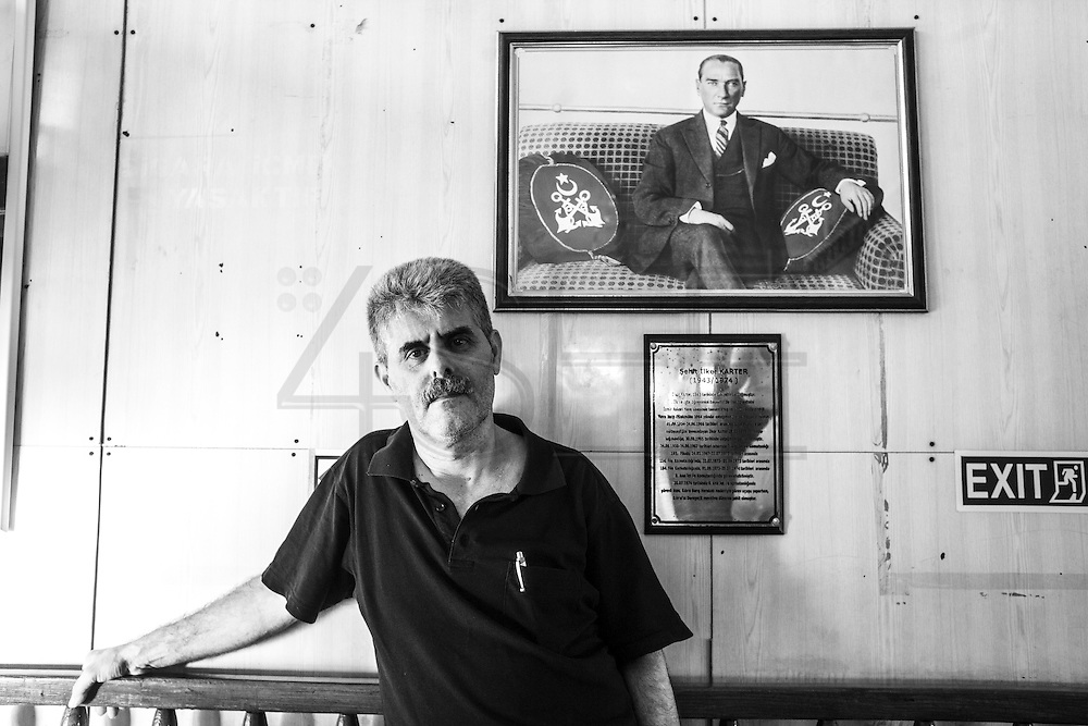A man poses in front of Mustafa Kemal Ataturk portrait, inside one of Istanbul's ferry boats (vapur). Ataturk is considered to be the founder of The Turkish Republic.