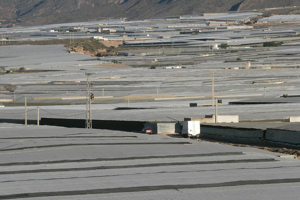 """EUROPE - SPAIN - EL EJIDO ; Illegal Immigration - VEGETABLE & FRUIT Production in Andalusia ; EL PLASTICO ; Exploitation of African workers;.The fruits and vegetables grown in the area are worth about $1.8 billion a year. Most of the workers are Moroccans, often called """"Moros"""" in reference to the Moors who ruled southern Spain for 700 years; Europa - SPANIEN - Landwirtschaft.Die Region um El Ejido, Provinz Almeria in Andalusien, gilt als Europas  größter agrarindustriell genutzter """"Wintergarten"""". Unter ca. 36.000 Hektar Plastik (Treibhäusern) wird ganzjährig Obst und Gemüse angebaut, welches zum Großteil in Supermärkten in Nordeuropa, Deutschland und England verkauft wird... Unter den Plastikplanen werden ca. 60.000, meist illegale Einwanderer aus Marokko, Schwarzafrika, Osteuropa beschäftigt. Arbeitsschutz und Mindestlöhne werden nicht eingehalten. .HIER: Blick über die Treibhäuser, die durch die Plastikgewächshäuser verschandelte Landschaft; südlich von El Ejido....23.03.2007.Copyright: Christian Jungeblodt"""