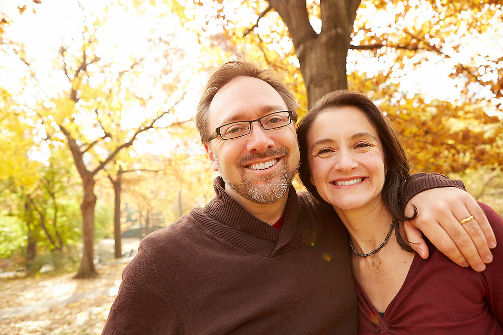 Lifestyle image of happy middle age couple hugging in park during autumn