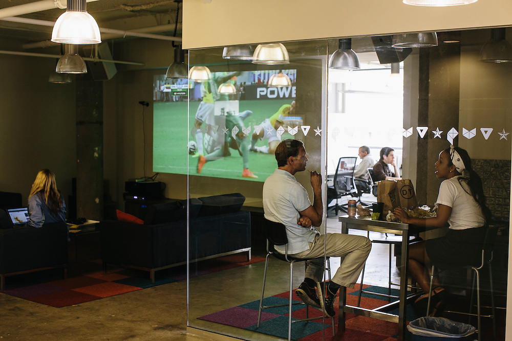 Employees at VOX Media, work while World Cup games show at their office in Washington DC.