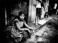 "(Intro) Selling Spring, or ""Baishun"" in Japanese, reflects age-old attitudes towards prostitution, this form of servitude.  The portraits examine the humanity of young women, many of whom would not even provide a first name, inlisted in selling their spring. ..(Caption) Unaffected by the economic upturn in Mumbai, India.  Worn out sex worker gazes out from her stoop on Falklands Road, the heart of the red light district, Mumbai, India.  Some sources put the level of HIV infection at 60% among Mumbai's sex workers because of low condom use."