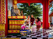 14 APRIL 2019 - DES MOINES, IOWA: A woman at a statue of the Buddha during Lao New Year, also called Songkran,  observances at Wat Lao Buddhavath in Des Moines. Several thousand Lao people live in Des Moines. Most came to the US after the wars in Southeast Asia. Songkran is celebrated in Theravada Buddhist countries (Sri Lanka, Myanmar, Thailand, Laos, and Cambodia) and in Theravada Buddhist communities around the world.       PHOTO BY JACK KURTZ