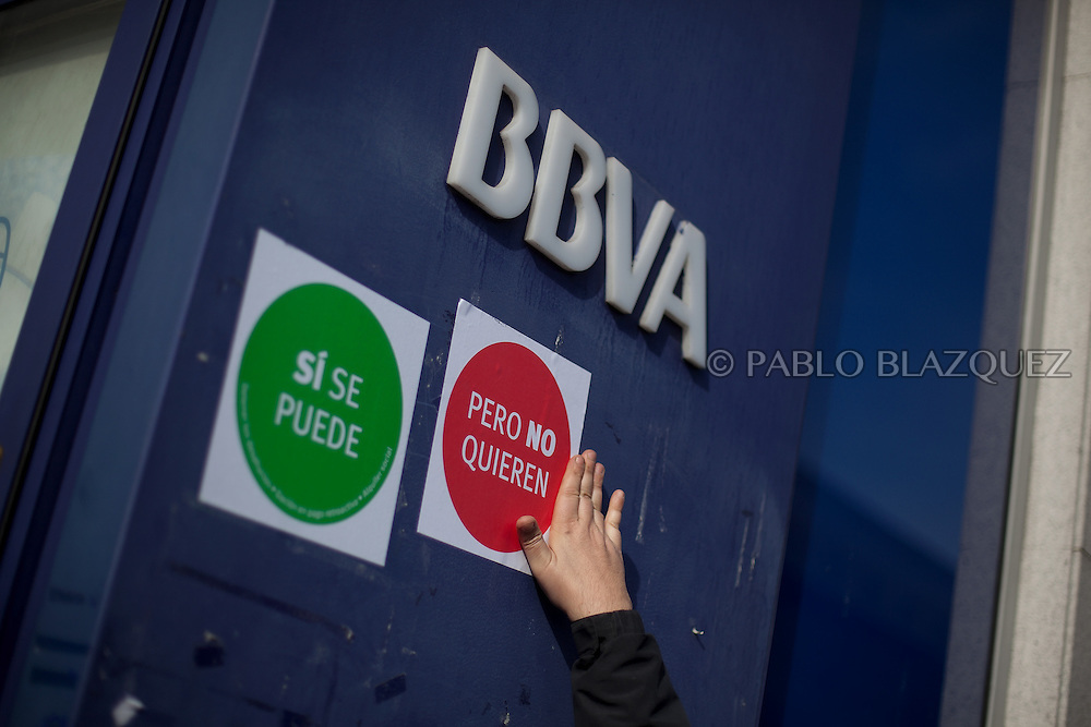 An anti eviction activist stamps stickers reading 'Yes we can, but they don't want' at BBVA bank's wall before an 'escrache' near the house of Spain's President of Parliament Jesus Posadas on April12, 2013 in Madrid, Spain. The Mortgage Holders Platform (PAH) and other anti evictions organizations have been organizing 'escraches' for several weeks under the slogan 'There are lives at risk' to claim the vote for a Popular Legislative Initiative (ILP) to stop evictions and facilitate social rent, outside Popular Party deputies' houses and offices. 'Escraches' are a form of peaceful protest that were used in Argentine in 1995 to publically denounce pardoned members of the dictatorship for their crimes at their doorsteps.