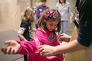 Mackenzie Visingard, 7, of Victor, whose family is adopting a brother from Korea, tries on a Korean outfit at the fourth annual Korean Lunar New Year celebration at Brooks Hill School in Fairport on Saturday, February 7, 2015.