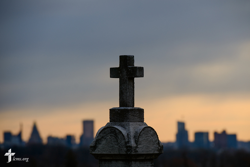A headstone and cross frames the foreground against the Baltimore skyline on Palm Sunday, March 25, 2018. LCMS Communications/Erik M. Lunsford