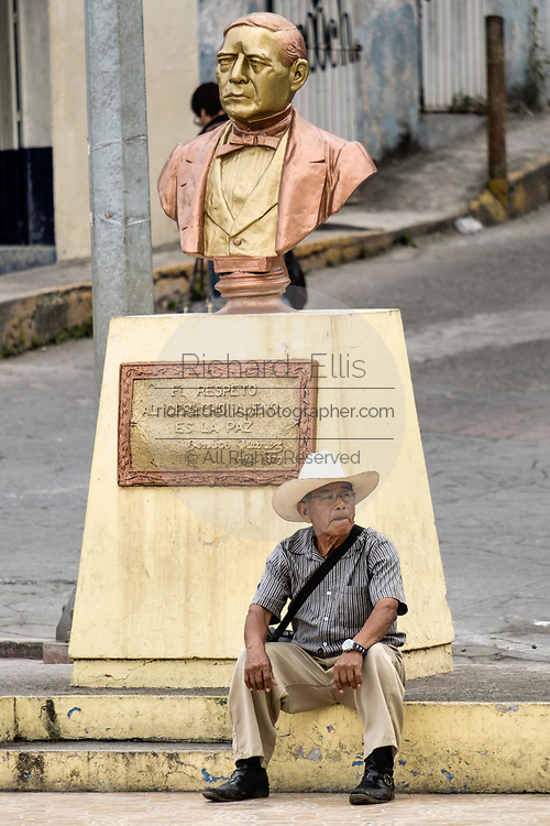A Mexican sits under a bust of Benito Juarez in Papantla, Veracruz, Mexico.