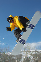 Teenage snowboarder jumping