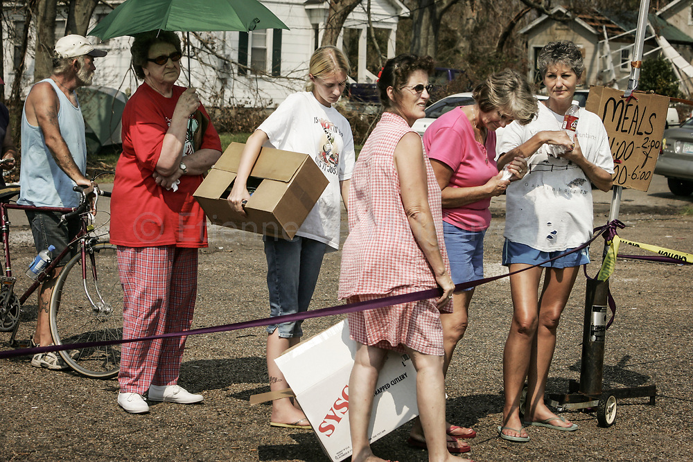 Local residents wait in a free meal distribution line as the whole Mississipi coast was blacked out. Long Beach, Mississippi. 05 September 2005.