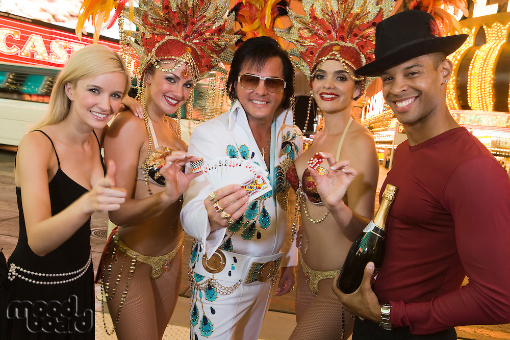 Tourists, Elvis impersonator and female dancers having fun
