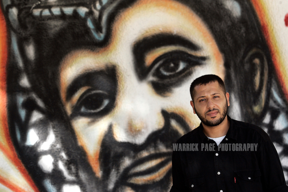 GAZA CITY, GAZA STRIP - AUGUST 20: Mohammed Fouad stands in front of one of his portraits of Yasser Arafat , August 20, 2009, Gaza City, Gaza Strip. Mohammed has been to jail five times since Hamas took over Gaza an forbid artists from painting or writing any pro-Fatah graffiti. Since the two factions became bitter rivals, there is little room for  political dissent within either territory. (Photo by Warrick Page)
