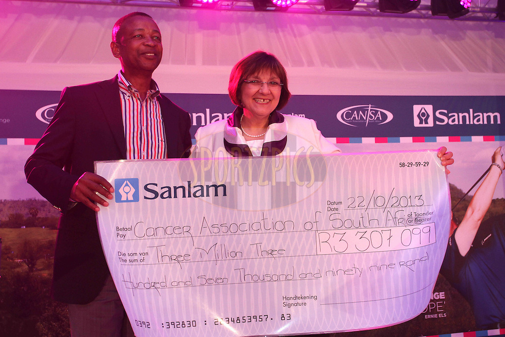 Temba Mvusi Chief Executive Market Development Sanlam presents a cheque to Sue Janse van Rensburg  (Cansa) during the Prize Giving Dinner of the Sanlam Cancer Challenge Finals held at the Gary Player Country Club in Sun City near Johannesburg on the 22nd October 2013<br /> <br /> Photo by Shaun Roy - SPORTZPICS